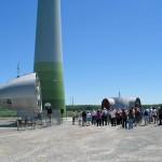Groupe de visiteurs au pied d'une éolienne