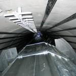 Vue de l'intérieur de la tour depuis la base jusqu'au sommet. On peut y voir l'échelle pour accéder au sommet et les câbles de tensionnement.