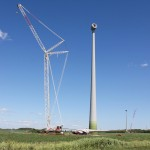 Vue d'une éolienne avec, au sol, les pales installées sur le rotor